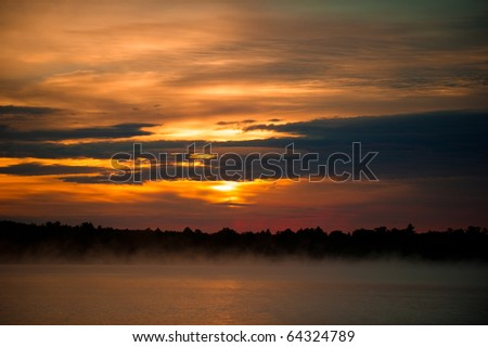 Sunset over misty lake in Wisconsin - stock photo