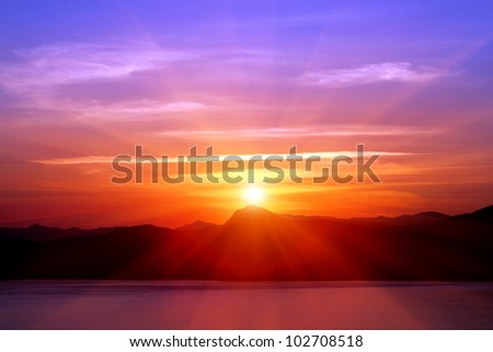 sunset over mountains near sea - stock photo