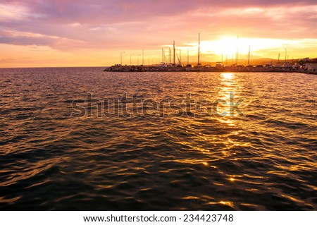 Sunset over Nikiti port with copy-space on the sea surface - stock photo