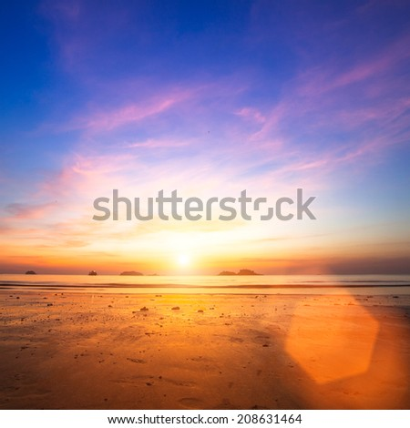 Sunset over ocean at low tide. - stock photo