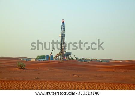 """Sunset over oil field in the Red sand """"Arabian desert"""" near Dubai, United Arab Emirates - stock photo"""