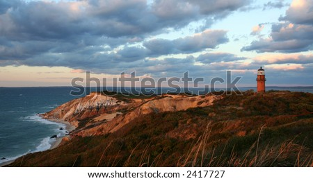 Sunset over red cliffs and lighthouse at Martha's Vineyard - stock photo