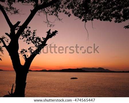 Sunset over river Brahmaputra with silhouette of trees and boat in the background.