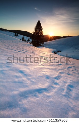 sunset over river in snowy mountains