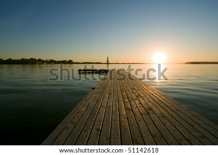sunset over river, wooden quay at foreground - stock photo