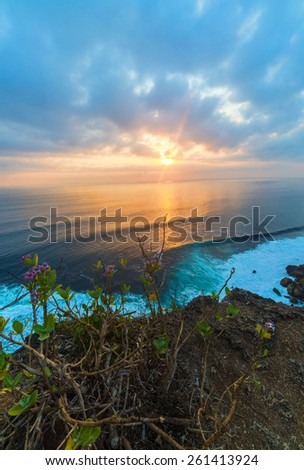 Sunset over rocky coast of Indian Ocean. Bali island, Indonesia - stock photo