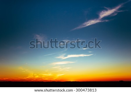 Sunset Over Rural Countryside Field. Bright Blue, Orange And Yellow Colors Sunrise Sky And Dark Ground.