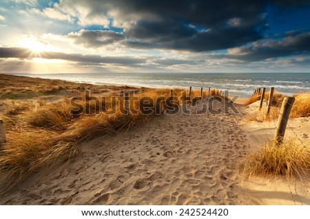 sunset over sand path to North sea, Holland - stock photo