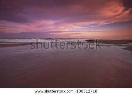 Sunset over sandy beach on the Atlantic shore - stock photo