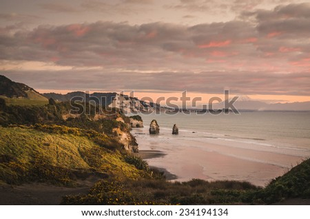 sunset over sea shore rocks and mount Taranaki New Zealand - stock photo