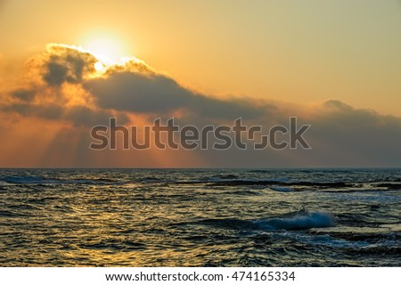 Sunset over sea with sun beams through clouds