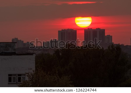 Sunset over skyline with bright Sun disk between two buildings. Moscow, Russia.