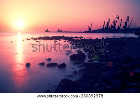 Sunset over stone beach with port - stock photo
