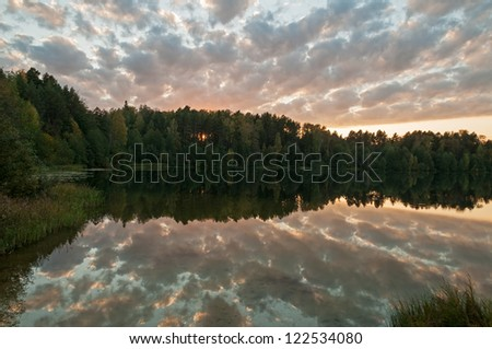Sunset over Svetloyar Lake with bush in foreground and forest along bank reflecting in calm water