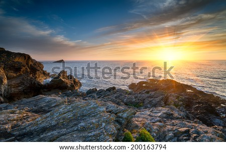 Sunset over the Atlantic from the cliffs at West Pentire headland at Crantock near Newquay in Cornwall - stock photo