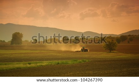 sunset over the cultivated farmland - stock photo