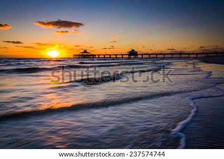 Sunset over the fishing pier and Gulf of Mexico in Fort Myers Beach, Florida. - stock photo