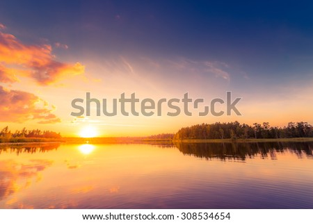 Sunset over the forest lake. View from the boat, image in the orange-purple toning - stock photo