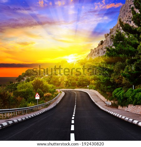 Sunset over the Highway in mountains - stock photo