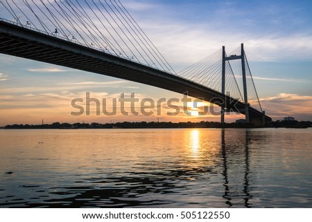 Sunset over the Hooghly river bridge - silhouette view. Vidyasagar bridge is the longest cable-stayed bridge in India.