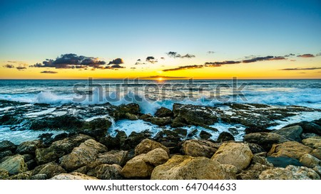 Sunset over the horizon with a few clouds and the rocky shores of the west coast of the tropical Hawaiian island of Oahu