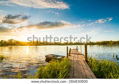 Sunset over the lake in the village. View from a wooden bridge - stock photo