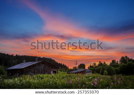 sunset over the old village barn overgrown with flowers - stock photo