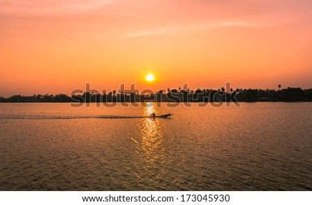 sunset over the river with the fisherman on the boat - stock photo