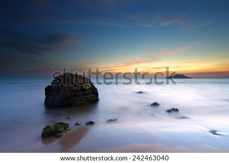 Sunset over the rocks and the ocean. Dramatic sky - stock photo