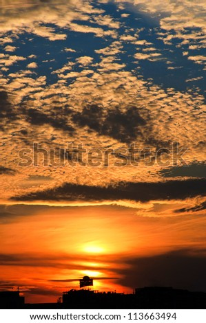 Sunset over the roofs - stock photo
