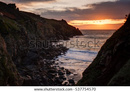 Sunset over the sea. Almost silhouetted rocky coast on foreground.