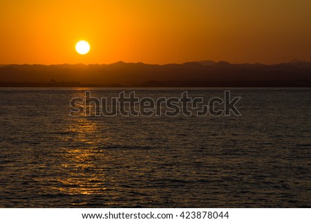 Sunset over the sea; silhouettes of distant mountains at the coastline standing out against of bright sky (Red sea, Egypt) - stock photo
