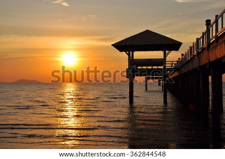 Sunset over the sea with jetty at Bangsaen Thailand.