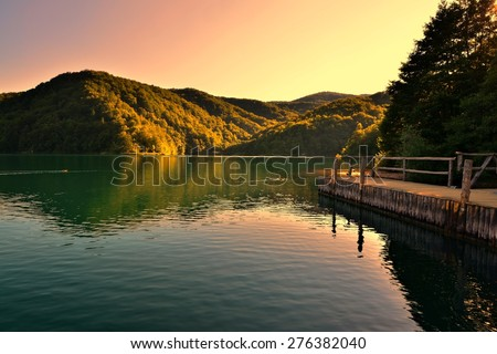 Sunset over the serene waters of Plitvice Lakes National Park with reflections, Croatia - stock photo
