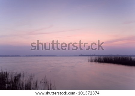 sunset over the water with pink clear sky - stock photo