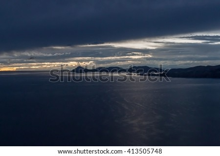 Sunset over Titicaca lake, behind Isla del Sol, Bolivia - stock photo