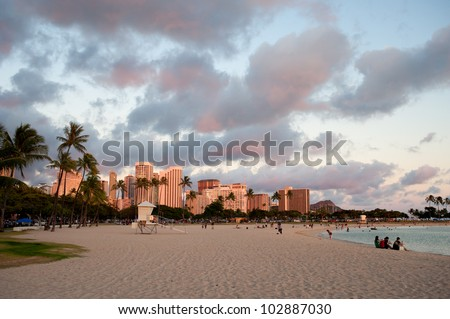 Sunset over Waikiki beach with modern buildings in the back - stock photo