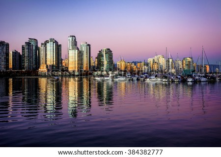 Sunset partially illuminates the glass buildings on the waterfront, with boats on the right