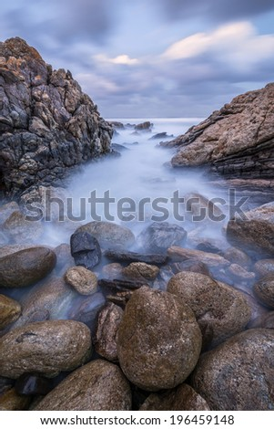 Sunset photograph of misty waves crashing on the rocks by the South Coast in South Africa