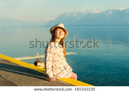 Sunset portrait of adorable little girl sitting next to lake with closed eyes and smile on her face, wearing a hat and beautiful dress - stock photo
