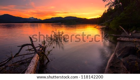 Sunset reflect in lake with mountains in distance and log in the water - stock photo