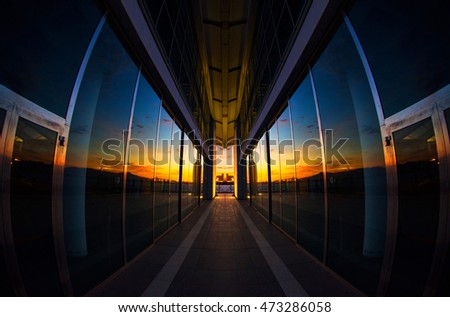 Sunset reflected on a modern glass building with perfect specular simmetry - horizzontal shoot