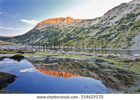 sunset reflection on the fish lake in Rila mountain - stock photo