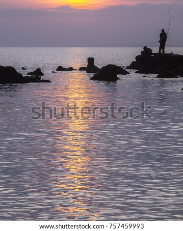 Sunset reflection on the ocean as a silhouetted  fisherman stands on rocks, Thailand