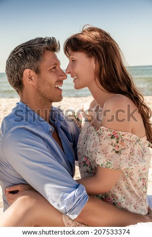 sunset relaxing lovely couple on the beach - stock photo