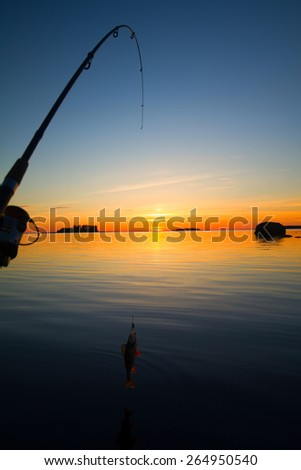 Sunset river perch fishing with the boat and a rod - stock photo