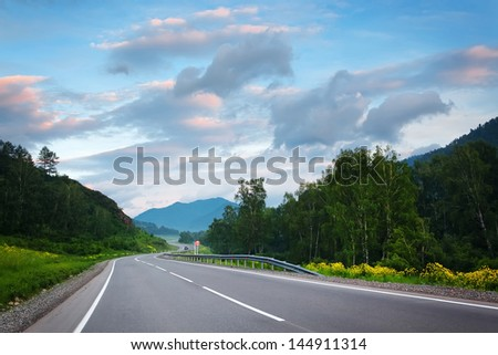 sunset road at mountains - stock photo