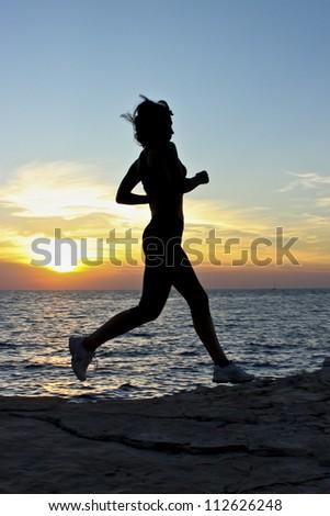 Sunset run Description: Woman running by the coast at sunset - stock photo