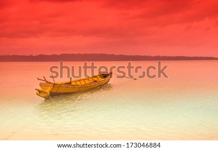 sunset scene at sea beach with a wooden boat