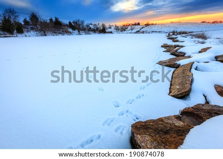 Sunset scene on a frozen lake - stock photo